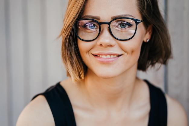 Zamyka w górę portreta młoda szczęśliwa kobieta w szkłach z ładnym uśmiechem i niebieskimi oczami, krótkie włosy, przypadkowy ubierający. koncepcja szczęśliwych ludzi.