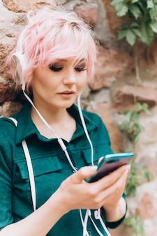 Zamyka w górę portreta młodej kobiety freelancer słucha muzyka na słuchawkach z różowym ostrzyżeniem