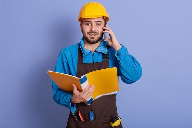 Zamyka w górę portreta młody atrakcyjny brodaty budowniczy ma rozmowę przez telefonu i trzyma papierową falcówkę w rękach, ubiera błękitną koszula, brown fartucha, żółty hełm. koncepcja budowlana i inżynierska.