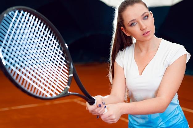 Zamyka w górę portreta młody atrakcyjny kobiety gracz w tenisa trzyma tenisowego kant