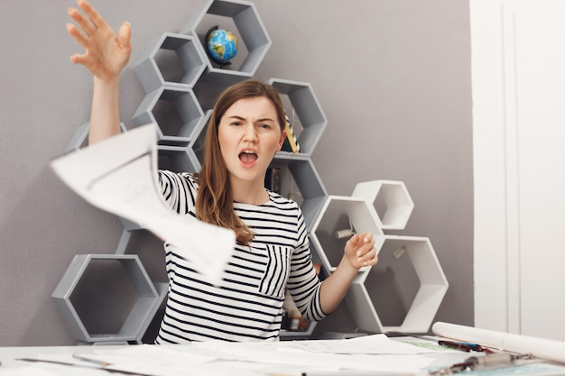 Zamyka w górę portreta młody nieszczęśliwy przystojny żeński niezależny inżynier wyrzuca dokumenty robocze z gniewnym i niezadowolonym wyrazem, po tym, jak klient odrzucił całą pracę.