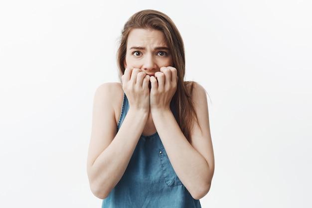Zamyka w górę portreta nieszczęśliwa młoda caucasian ciemnowłosa rozsądna dziewczyna w błękitnej koszulowej mieniu wręcza blisko twarzy, z dbającym wyrażeniem. kobieta boi się oglądać straszny film zb