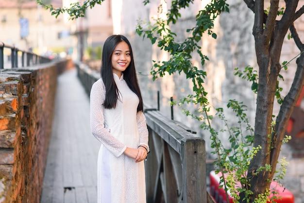 Zamyka w górę portreta piękna azjatykcia kobieta ubierająca w ao dai bielu sukni stojakach blisko drzewa na drewnianym moscie.