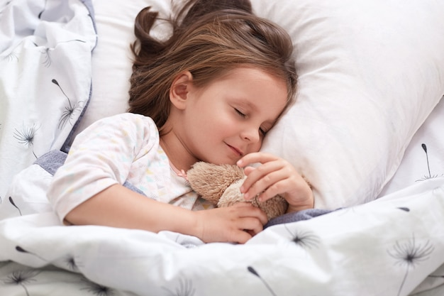 Zamyka w górę portreta piękna dziewczyna śpi w piżamie w łóżku z jej misiem, kłama na poduszce z zamkniętymi oczami, uroczego ślicznego żeńskiego dzieciaka ma ciemne włosy. pojęcie czasu dzieciństwa i poranka.