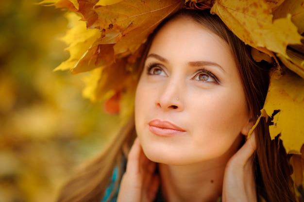 Zamyka w górę portreta piękna dziewczyna w ciemnej kamizelce. na głowie jest bujny wieniec z jesiennych liści. dziewczyna odwraca wzrok.