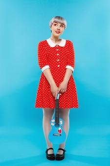 Zamyka w górę portreta piękna lalkowata dziewczyna jest ubranym czerwieni suknię trzyma ukulele nad błękit ścianą z krótkim jasnofioletowym włosy