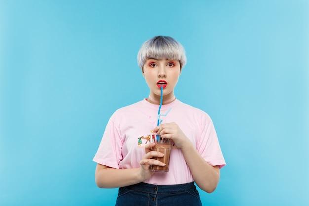 Zamyka w górę portreta piękna lalkowata dziewczyna z krótkim jasnofioletowym włosy w różowym tshirt pije sok nad błękit ścianą