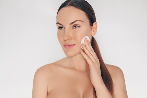 Zamyka w górę portreta pięknej przyrodniej naga naturalna piękno kobiety oczyszczającej twarzy perfect skóry biel odizolowywająca ściana. czyszczenie leczenia opieki zdrowotnej. koncepcja spa skincare.