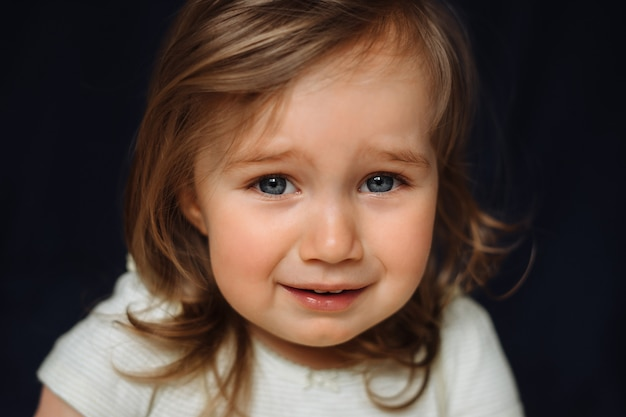 Zamyka w górę portreta płaczu małe dziecko na czerni