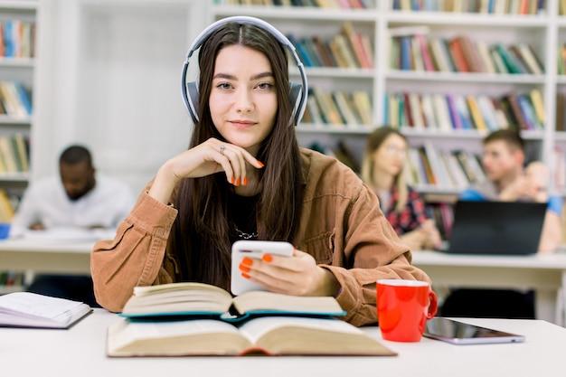 Zamyka w górę portreta powabny śliczny uśmiechnięty młoda dziewczyna uczeń, siedzący w bibliotece przy stołem z wiele książkami, słuchający muzykę w słuchawkach