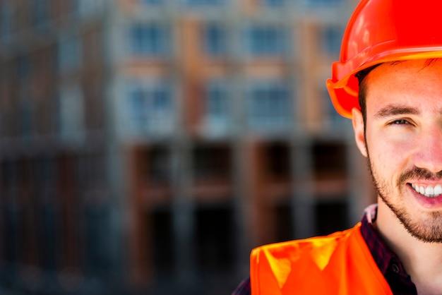 Zamyka w górę portreta pracownik budowlany patrzeje kamerę