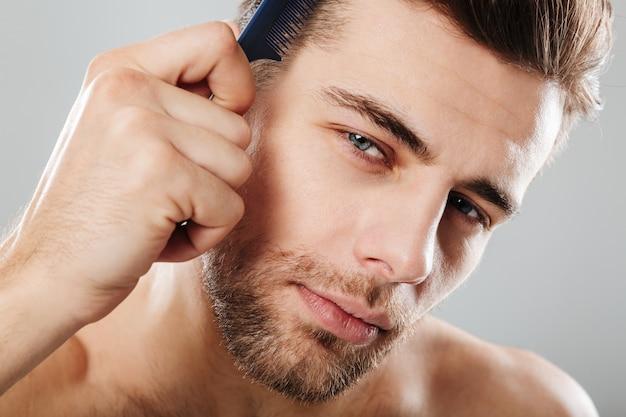 Zamyka w górę portreta przystojny mężczyzna czesze jego włosy