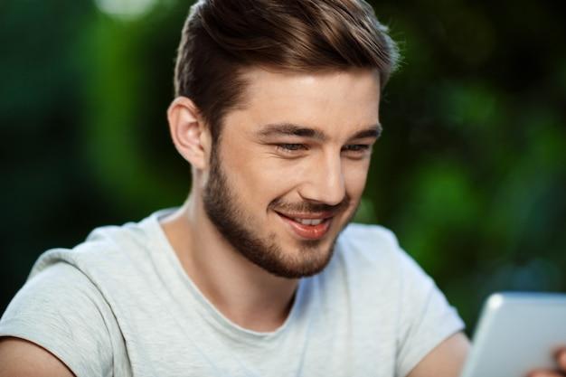 Zamyka w górę portreta przystojny rozochocony uśmiechnięty młodego człowieka obsiadanie przy stołem w na otwartym powietrzu cukiernianej mienie pastylce patrzeje na ekranie.