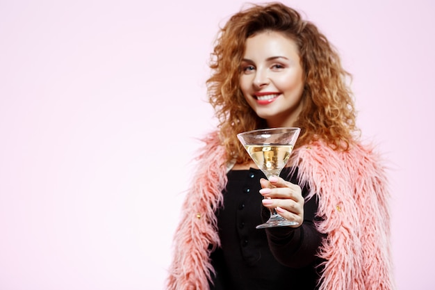 Zamyka w górę portreta rozochoconej uśmiechniętej pięknej brunetki kędzierzawa dziewczyna trzyma koktajlu szkło nad biel ścianą w różowym futerkowym żakiecie