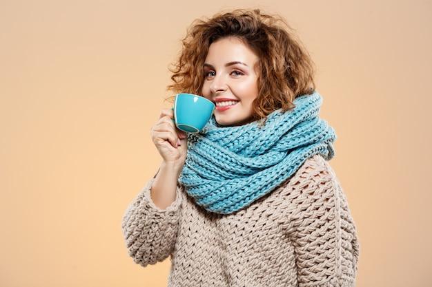 Zamyka w górę portreta rozochoconej uśmiechniętej pięknej brunetki kędzierzawa dziewczyna w trykotowym pulowerze i szarym neckwarmer trzyma filiżankę nad beż ścianą