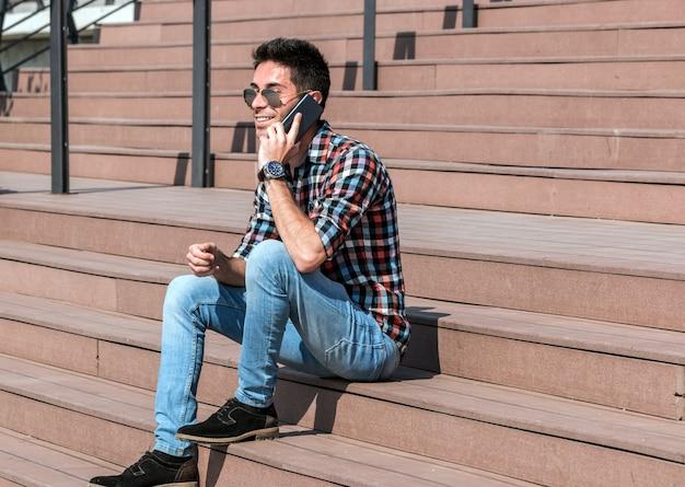 Zamyka w górę portreta rozochocony mężczyzna używa telefon komórkowego i śmiać się