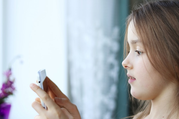 Zamyka w górę portreta śliczna mała dziewczynka patrzeje telefon