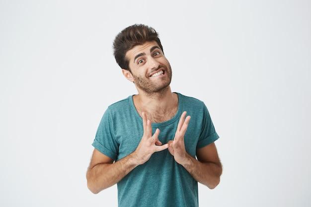 Zamyka w górę portreta śmieszny elegancki hiszpański facet w błękitnej koszulce, gryźć wargi i gestykulować rękami wyrażającymi czuć się super niezręcznie. język ciała.