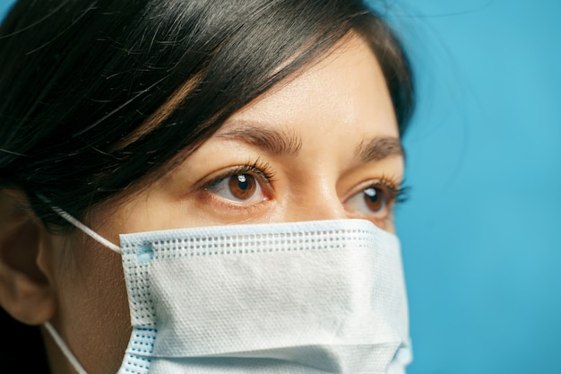 Zamyka w górę portreta smutna młoda azjatykcia kobieta w ochronnej medycznej masce na błękitnym tle. koncepcja strachu i samotności
