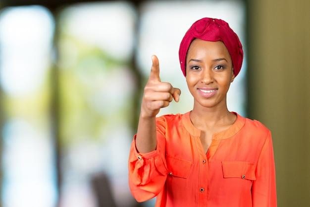 Zamyka w górę portreta szczęśliwa biznesowa kobieta wskazuje palec