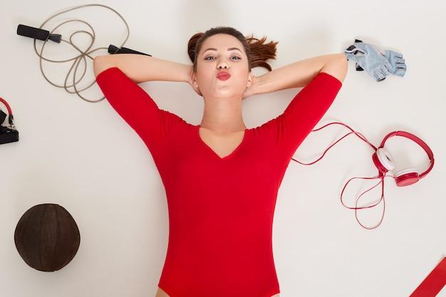 Zamyka w górę portreta szczęśliwa kaukaska kobieta kłaść na biel powierzchni otaczającej różnego sportowego wyposażenie: expander, sprawności fizycznych rękawiczki
