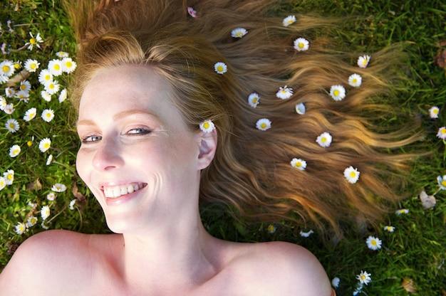 Zamyka w górę portreta szczęśliwa kobieta ono uśmiecha się z kwiatami w włosy