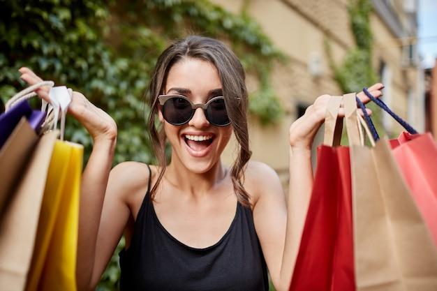 Zamyka w górę portreta szczęśliwa radosna młoda ciemnowłosa caucasian kobieta patrzeje w kamerze z zakładek szkłami i czarna koszula z rozpieczętowanym usta i szczęśliwym wyrażeniem, trzyma kolorowe torby na zakupy w rękach. żołnierz amerykański