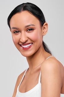 Zamyka w górę portreta szczęśliwa uśmiechnięta afroamerykańska dziewczyna z świeżą zdrową skórą
