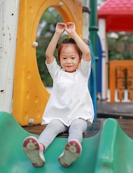 Zamyka w górę portreta szczęśliwa uśmiechnięta dzieciak dziewczyna bawić się suwaka na boisku