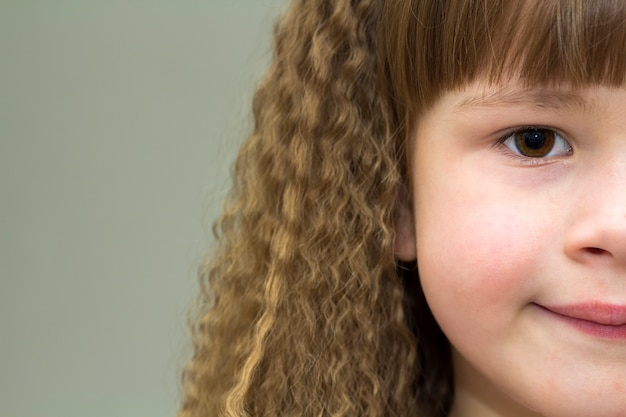 Zamyka w górę portreta szczęśliwa uśmiechnięta mała dziewczynka z pięknym gęstym włosy. widok części