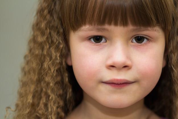 Zamyka w górę portreta szczęśliwa uśmiechnięta mała dziewczynka z pięknym gęstym włosy