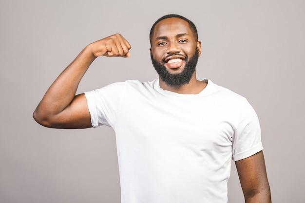 Zamyka w górę portreta szczęśliwy młody amerykanina afrykańskiego pochodzenia mężczyzna napina bicep mięsień odizolowywającego przeciw popielatemu tłu.
