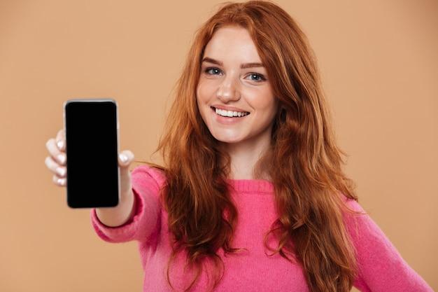 Zamyka w górę portreta uśmiechnięta atrakcyjna rudzielec dziewczyna pokazuje smartphone