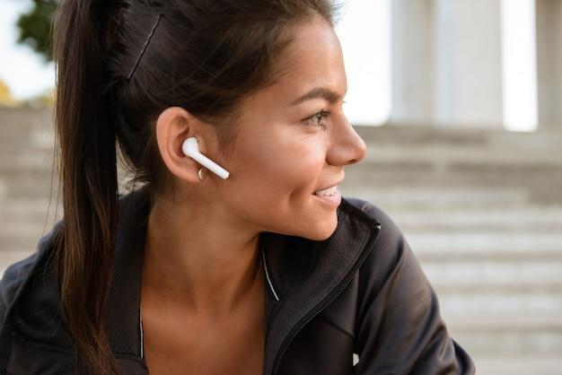Zamyka w górę portreta uśmiechnięta sprawności fizycznej kobieta w słuchawkach