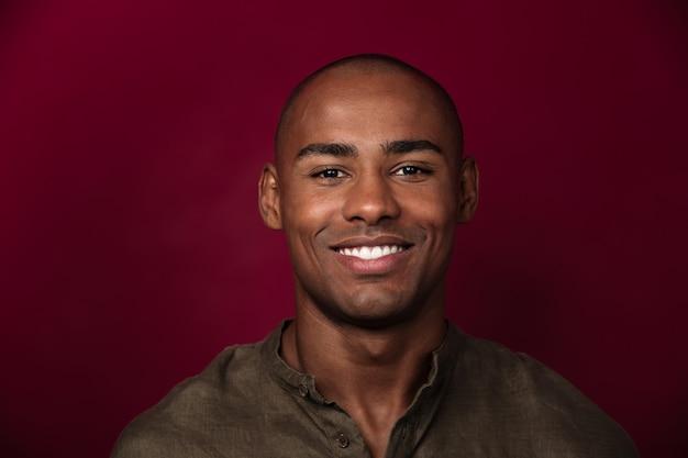 Zamyka w górę portreta uśmiechnięty afrykański mężczyzna patrzeć