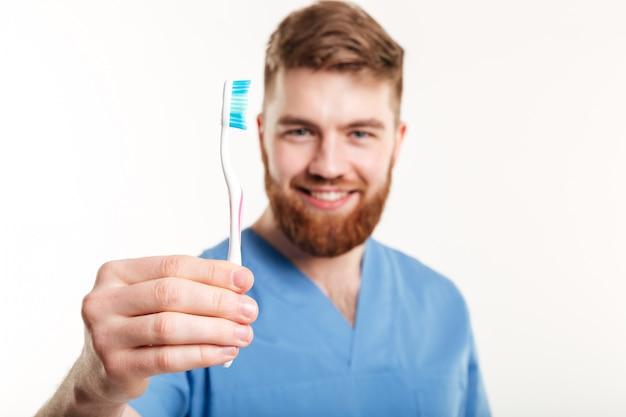 Zamyka w górę portreta uśmiechnięty męski dentysta pokazuje toothbrush