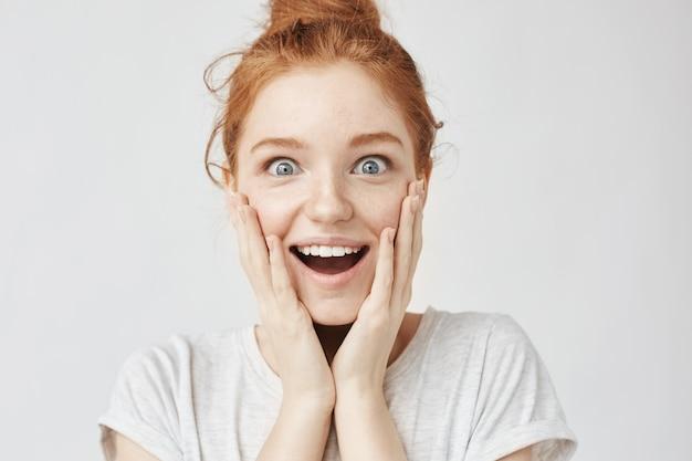 Zamyka w górę portreta zdziwiona szczęśliwa piegowata rudzielec kobieta