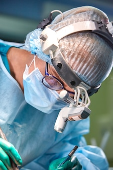 Zamyka w górę portreta żeńskiego chirurga doktorska jest ubranym ochronna maska i kapelusz podczas operaci. opieka zdrowotna, edukacja medyczna, koncepcja chirurgii.