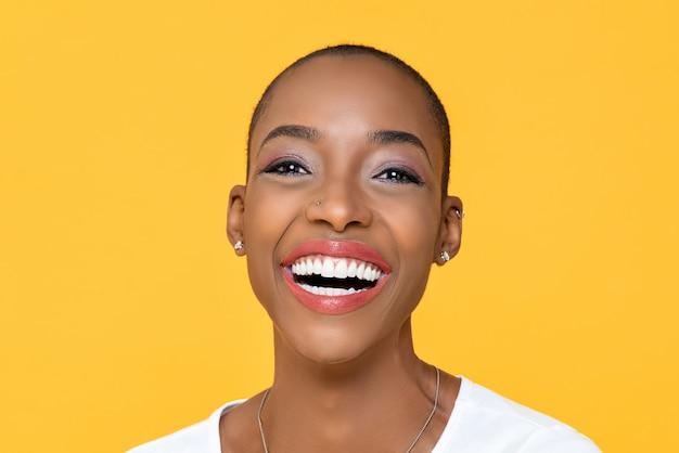 Zamyka w górę portreta życzliwa szczęśliwa amerykanin afrykańskiego pochodzenia kobieta ono uśmiecha się na odosobnionej kolorowej kolor żółty ścianie