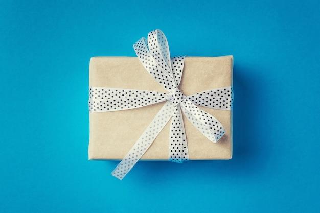Zamyka w górę prezenta pudełka z białym faborkiem na błękitnym tle, odgórny widok