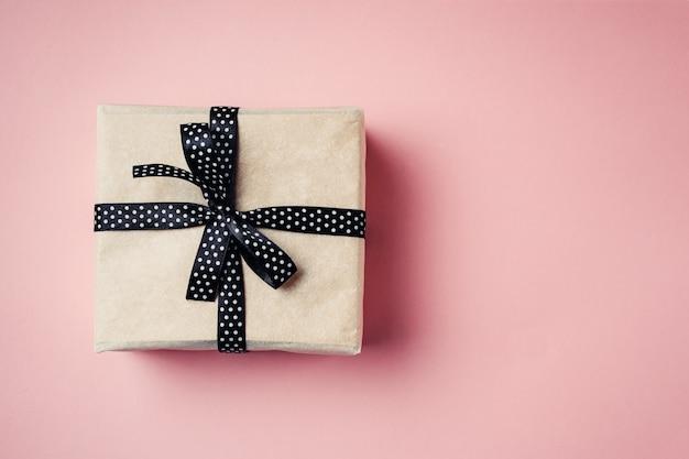 Zamyka w górę prezenta pudełka z czarnym faborkiem na różowym tle, odgórny widok