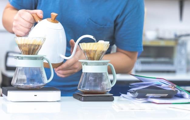 Zamyka w górę przyrodniej długości barista robi kawowemu filtrowi w kawiarni