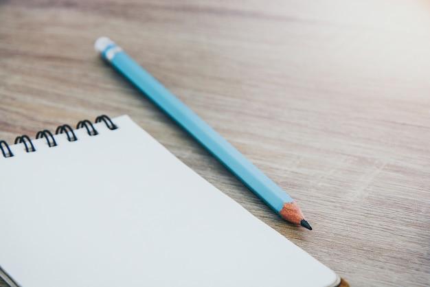 Zamyka w górę pustego otwartego notatnika i błękitnego koloru ołówka na drewnianym stołowym tle