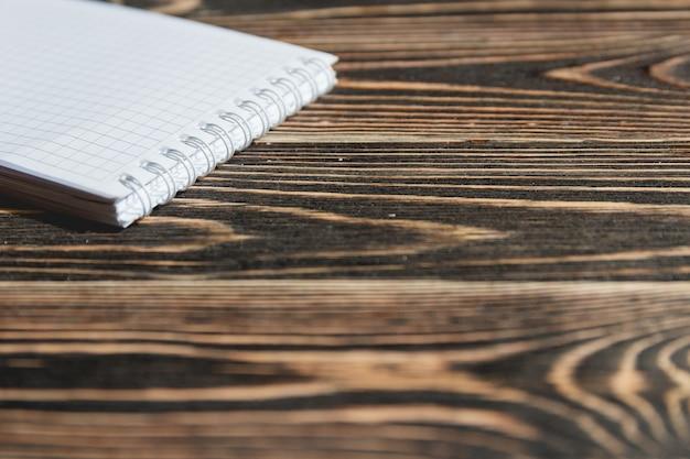 Zamyka w górę pustej notatki książki na grunge drewnie