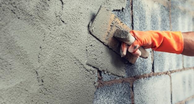Zamyka w górę ręka pracownika gipsowania cementu na ścianie dla budować dom