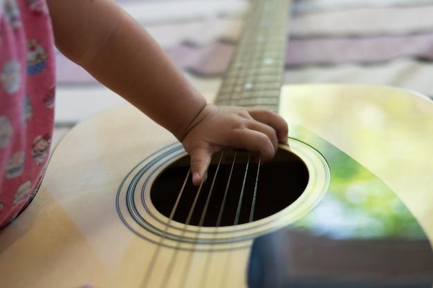 Zamyka w górę ręki dziecka bawić się gitarę