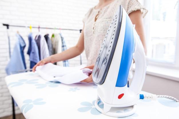 Zamyka w górę ręki kobiety prasowanie odziewa na stole