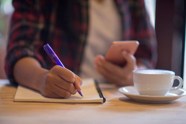 Zamyka w górę ręki kobiety writing pięknego notatnika z filiżanką w sklep z kawą