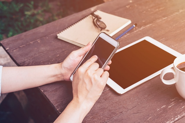 Zamyka w górę ręki mienia i używa telefon w sklep z kawą z rocznikiem tonującym.