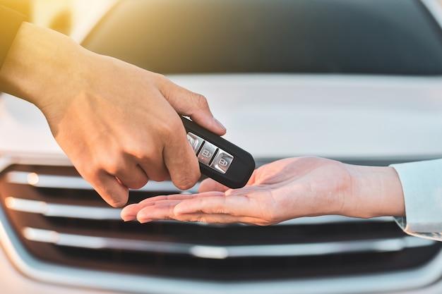 Zamyka w górę ręki mienia klucza sprzedaży samochodowego pojęcia, daje kluczowemu samochodowi i bierze